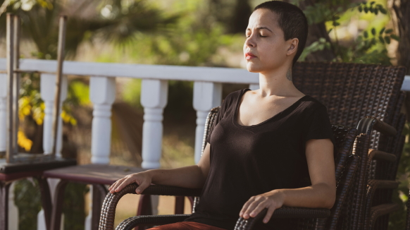 A woman closes her eyes and relaxes in a chair on an outdoor patio