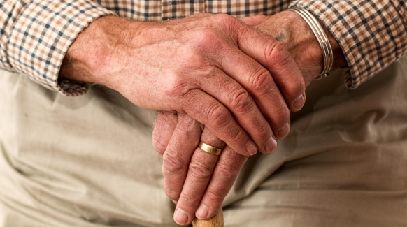 Close-up photo of a patient with Parkinson's Disease resting his hands on a cane