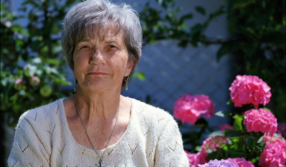 An elderly woman in a white blouse looks straight ahead as she sits outside in front of pink and purple flowers