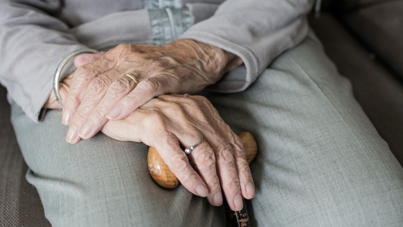 A woman with dysphagia rests her hands in her lap as she holds her wooden cane