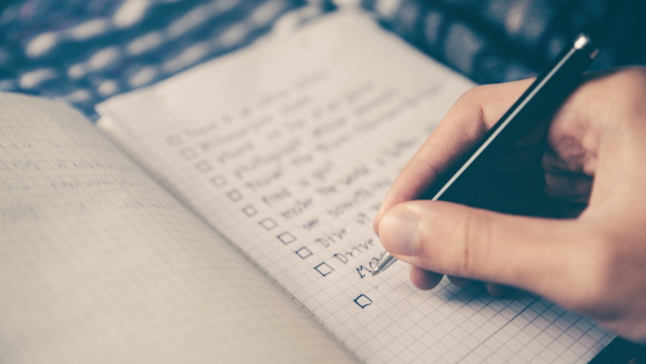 Close-up photo of a notebook lying flat as an individual's right hand uses a black pen to write a checklist