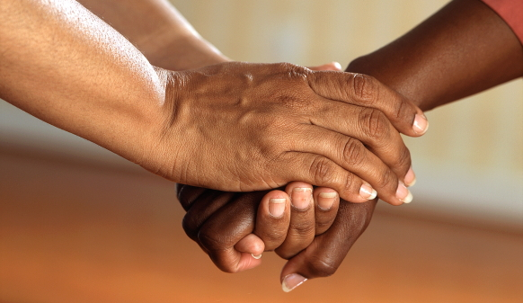 Close-up photo of two individuals holding one another's hands in comfort
