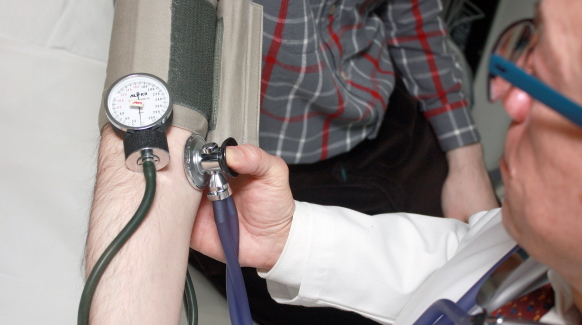 A physician holds a blood pressure monitor to a patient's arm