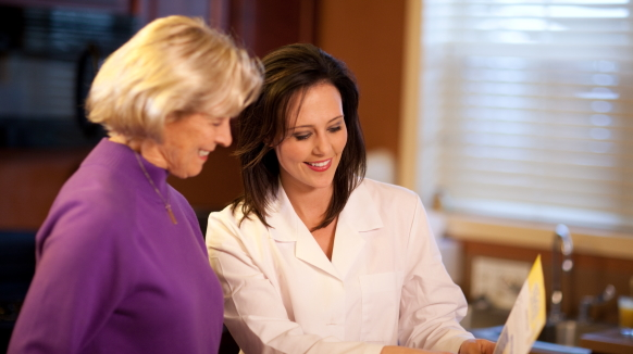 A speech-language pathologist in a white coat points to a piece of paper as she discusses exercises with a patient