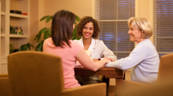 A healthcare professional explains dietary issues to a dysphagia patient and her caregiver