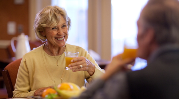 An elderly woman smiles and holds a glass of thickened orange juice as she sits across the table from her husband
