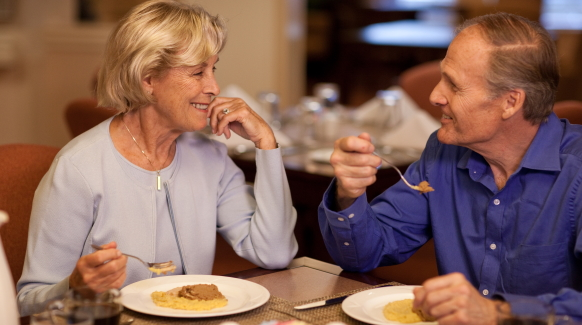 A couple sits at a table smiling at one another sharing a nutritious dysphagia-friendly meal