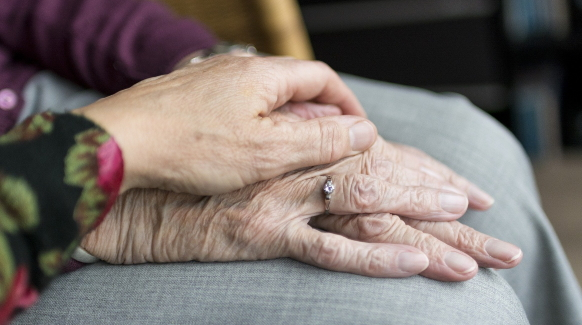 A caregiver rests her hand over her loved one's hands as a gesture of comfort