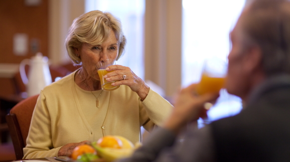 An elderly female in a yellow sweater holds a glass of thickened orange juice to her lips as she smiles across the table to her husband