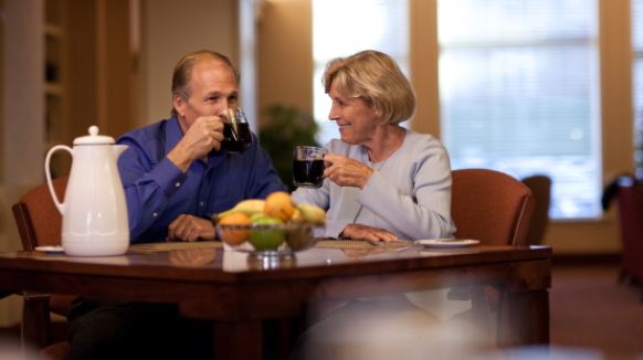 An elderly couple sits at a table sipping coffee while enjoying a meal together