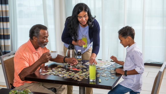 A family caregiver leans over a table where her son and her father are sipping beverages and working on a puzzle together