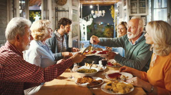 A family of six gathers around the dinner table to enjoy a holiday meal