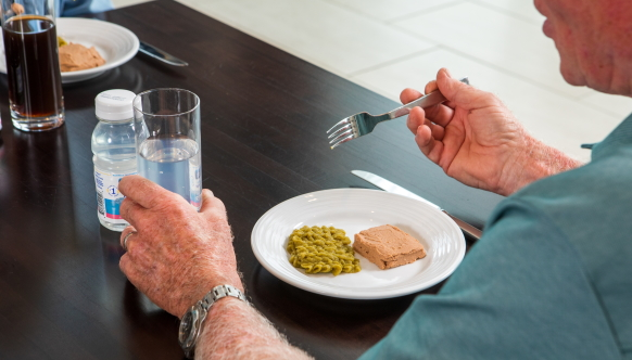 A man sitting at a table grips a glass of water while holding his fork over a plate of puréed food