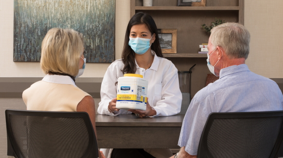 A healthcare professional seated at a table across from a man and a woman holds Thick-It® Original Food & Beverage Thickener