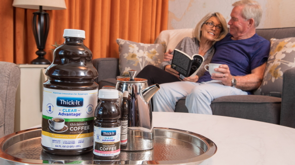 A tray of Thick-It® Clear Advantage® Thickened Coffee sits on a table in front of a man and a woman seated on a couch.