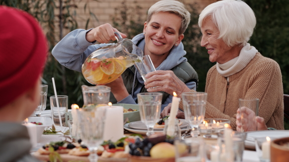 A young woman smiles as she pours a beverage from a pitcher into her grandmother's glass during a family meal outdoors.
