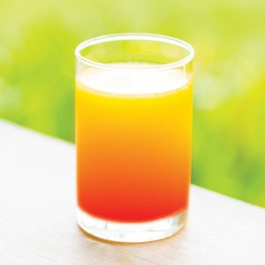 An orange and red Sunrise Mocktail in a glass
