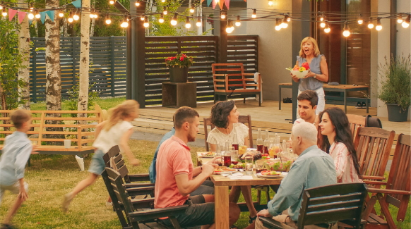 A family eats dinner together in their backyard.