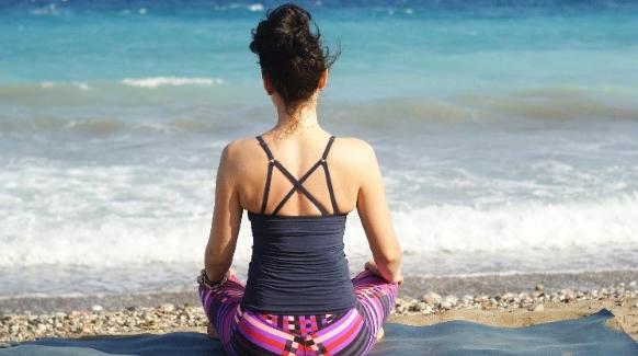 A woman practices yoga on the beach