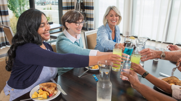 Three women seated at a table toast with glasses of thickened beverages over lunch.