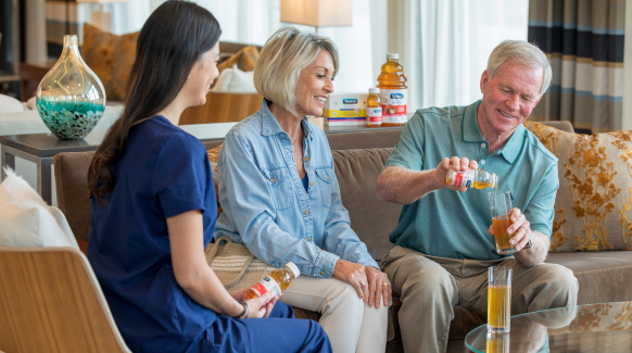 An elderly man, at right, sits on a tan couch pouring Thick-It® Clear Advantage® Thickened Apple Juice into a glass while his wife, center, and a female healthcare professional in blue scrubs, at left, smile and look on.