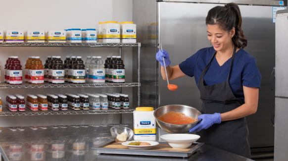 A female healthcare professional in blue scrubs and a black apron holds a ladle of red sauce, thickened with Thick-It® brand food & beverage thickeners, over a plate of pureéd food for dysphagia patients.