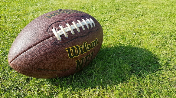 A football sits in a grass field.
